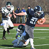 BRYAN EATON/Staff photo. A Pentucket defender grabs Triton running back Jake MacInnis.