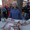 JIM VAIKNORAS/Staff photo Fiona Durphy from the Nock Middle School Clippers Club sells hot chocolate mix to raise money for homeless veteran at the annual Santa Parade and Tree Lighting in Market Square in Newburyport Sunday.