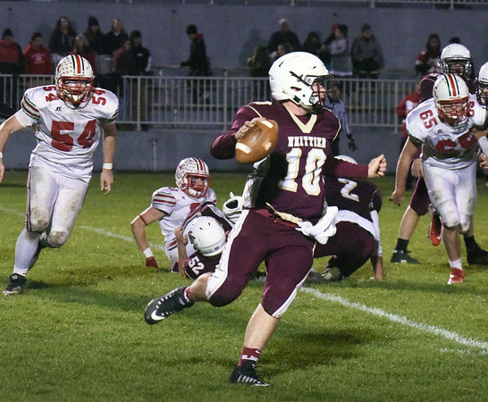 BRYAN EATON/Staff photo. Whittier quarterback Kevin Bradley looks to pass but runs the ball for yardage as Amesbury linemen Matthew Scibelli, left, and Benjamin Turbide head his way.