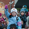JIM VAIKNORAS/Staff photo A girl wearing an Olaf hat waves to Santa and Mrs. Claus at the annual Santa Parade and Tree Lighting in Market Square in Newburyport Sunday.