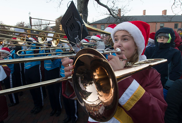 JIM VAIKNORAS/Staff photo  Sadie Fountain plays trombone with the combined Triton and Newburyport High School Bands at the annual Santa Parade and Tree Lighting in Market Square in Newburyport Sunday.