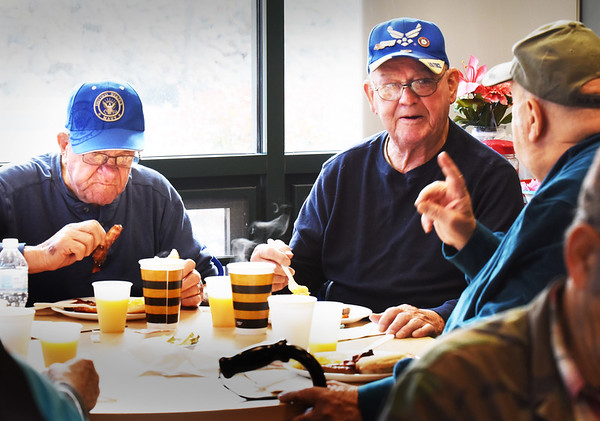BRYAN EATON/Staff photo. Three of a couple dozen U.S. military veterans enjoy a breakfast of English muffins, scrambled eggs, bacon, sausage and orange juice provided and prepared by the Amesbury Fire Department. Sharing stories at the Amesbury Senior Center, from left, Arthur Bibeau, Merrimac; Norman Bellevance and Mark Vedrani, both of Amesbury.