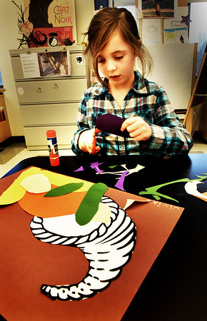 BRYAN EATON/Staff photo. Vivian Hebeisen, 6, cuts outs an eggplant to add to vegetables in the cornucopia she's making in art class at the Bresnahan School in Newburyport on Monday afternoon. The first-graders were learning about seasonal bounty and the shape of the goat's horn as a sign of plenty.