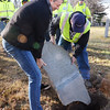BRYAN EATON/Staff photo. Bob Switzer helds Scott Eisenhaure of the Newburyport Department of Public Services put the stone back into place.