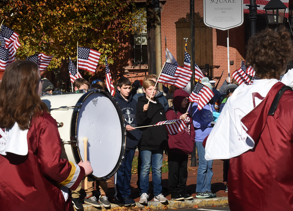 BRYAN EATON/Staff photo. Newburyport students line wave American flags as the Newburyport High School Marching Band heads to city hall in the Veterans' Day Parade.