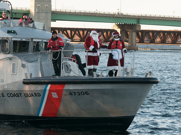 JIM VAIKNORAS/Staff photo Santa and Mrs. Claus make their way up the Merrimack courtesy of the US Coast Guard to the annual Santa Parade and Tree Lighting in Market Square in Newburyport Sunday.
