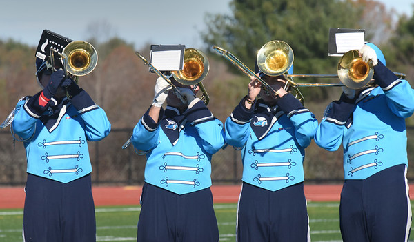 BRYAN EATON/Staff photo. The brass section of the Triton High Marching band performed as their team rushed onto the field during the Thanksgiving Day football game.
