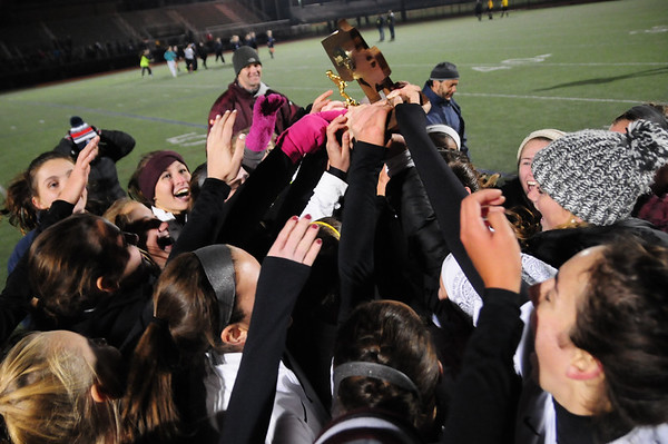 JIM VAIKNORAS/Staff photo The Newburyport girls soccer team reach to touch their trophy after defeating Swampscott to claim the North Sectional championship at Manning Field in Lynn Sunday Night.