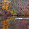 BRYAN EATON/Staff photo. One of two kayakers on Lake Gardner on Wednesday morning paddle past what's left of the foliage at the bottom of Powow Hill in Amesbury. Many leaves were blown off during the storm that came through starting on Sunday night.