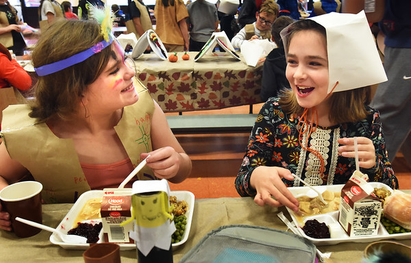 BRYAN EATON/Staff photo. Sadie Sullivan, left, and Hayden Taylor, both 9, chat over a Thanksgiving feast at the Cashman Elementary School in Amesbury on Monday afternoon. The third-graders have been learning about the Wampanoag tribe's lives, how they built their homes and taught the Pilgrims how to harvest corn among other things.