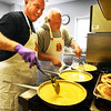 BRYAN EATON/Staff photo. Amesbury firefighters cooked breakfast for veterans at the Amesbury Senior Center on Wednesday. Whipping up scrambled eggs were Deputy Chief Jim Nolan and John Kane.