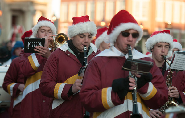 JIM VAIKNORAS/Staff photo The Newburyport High School Band makes their way down Water Street during the annual Santa Parade and Tree Lighting in Market Square in Newburyport Sunday