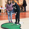 JIM VAIKNORAS/Staff photo Georgio Gioldasis, 11, and his sister Sophia, 14, play mini-golf at the Newburyport high school gym Friday. The annual event run by the junior class, which also included face painting and a putting contest raised money for the Jimmy Fund.