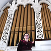 BRYAN EATON/Staff photo. Andrea DeGiovanni, the music director of the Belleville Congregational Church in Newburyport, poses in front of their 150 year-old organ. The church is having a fundraiser to renovate the organ and make repairs to the ceiling of the sanctuary.