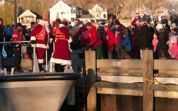 JIM VAIKNORAS/Staff photo Santa and Mrs. Claus step off the  US Coast Guard 44 footer at the annual Santa Parade and Tree Lighting in Market Square in Newburyport Sunday.