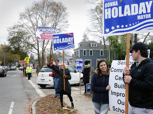 BRYAN EATON/Staff photo. Candidate suppporters wave to motorists on High Street in Newburyport outside the Newburyport Senior Center where residents of Wards 5 and 6 vote.