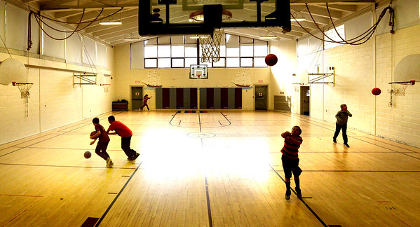 BRYAN EATON/Staff photo. Youngsters are silhouetted in the gymnasium at the Newburyport Rec Center as they shoot some basketballs. Despite the chilly weather, several were at the playground outside.