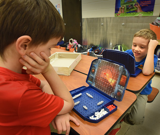 BRYAN EATON/Staff photo. Ben Pifalo, 8, left, gives Ethan LaPointe, 7, a refresher course in the game of Battleship at the Amesbury Recreational Department's afterschool program at Amesbury Elementary. Activities were kept indoors as the playground was wet with drizzle.