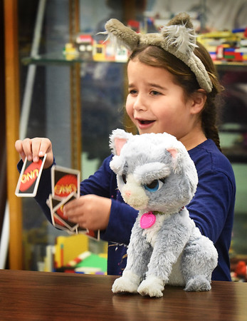 "BRYAN EATON/Staff photo. Jasmine Voltero, 6, appears not to like the hand in Uno that her friend Robert Bishop, 6, dealt her in the Boys and Girls Club in Salisbury's game room. She was wearing wolf ears and brought her robotic kitty cat as she said ""I really love animals."""