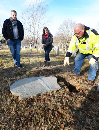 BRYAN EATON/Staff photo. Bob and Lore Switzer of Pepperell approach the gravestone of Lydia Smith, who died in 1745, with members of the Newburyport Department of Public Services, with foreman Alan Frost, right, at the Old Hill Burying Ground. They found the front portion of the stone at their Pepperell home and traced it to Newburyport and returned it to officials. Frost found the backing of the stone through records, pieced it together and replaced the stone yesterday on the 272nd anniversary of Smith's death.