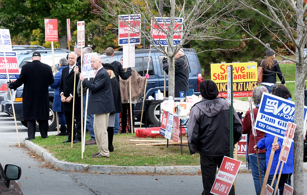 BRYAN EATON/Staff photo. Amesbury Mayor Ken Gray, at left facing motorists looking for a space to park, at Amesbury High School yesterday among signs of candidates for city council, is unopposed in his reelection bid. Voters will also decide whether to allow shops that sell marijuana.