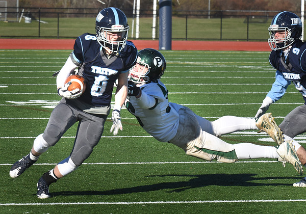 BRYAN EATON/Staff photo. Pentucket's Jacob Codair makes a flying grab onto Triton's Dylan Leavitt.