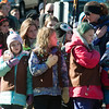 JIM VAIKNORAS/Staff photo Girl Scouts cover their hearts during the Pledge of Allegiance at Amesbury Middle School during the annual Veterans Day service Saturday.