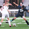 BRYAN EATON/Staff photo. Newburyport's #23 and Triton's Ben Hall go for the ball.