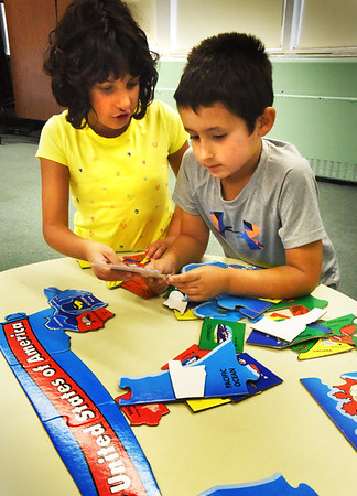 BRYAN EATON/Staff photo. Hannah Paulraj and Al Norman, both 8, and of Amesbury work on a puzzle of the United States in the gameboard room of the Boys and Girl on Wednesday. Hannah was looking for the piece that was her favorite state, Pennsylvania, because she was born there.