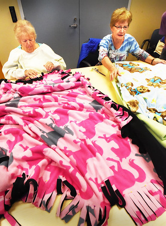 "BRYAN EATON/Staff photo. Laurette Dupuis, left, and Theresa Genest, both of Amesbury, meet with several others at the Amesbury Senior Center on Tuesdays for ""Blankets For Kids."" They get to socialize with each other and create different blankets which are donated to those in need."
