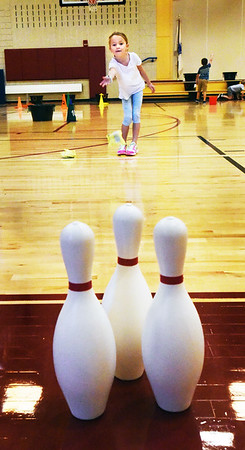 BRYAN EATON/Staff photo. First-grader Addison Forrest, 6, takes aim of some bowling pins with a bean bag in physical education class at the Bresnahan School in Newburyport. They were at different stations throwing underhand to work on their eye to hand coordination.