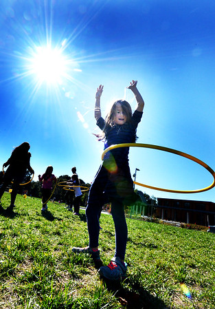 BRYAN EATON/Staff photo. Eva Moyles, 7, practices her hula hoop skills at Newburyport's Bresnahan School, which is tied to physical education class, under a sunny sky. The bright weather and warm temperatures are here throughout the weekend until Tuesday night when rain is in the forecast.