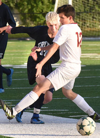 BRYAN EATON/Staff photo. Triton's Josh Rolfe heads for the ball that Noah Kirby overshot.
