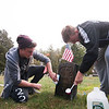 JIM VAIKNORAS/Staff photo Jack Crocker and Jack O'Keefe  clean the grave stone of Civil War veteran Jewett Rogers Sunday afternoon. They were two of about 50 Triton student volunteers to clean the graves of veteran's at South Byfield Cemetery.