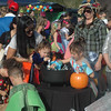DAVE ROGERS/Staff photo Little children dig into a basket of candy provided by the Amesbury Public Library, one of an estimated 45 vendors who set up trunks Saturday afternoon  inside the New England Sports Park in Amesbury. The trunks were part of the first annual Newburyport Trunk or Treat event.