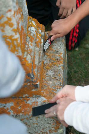 JIM VAIKNORAS/Staff photo Students scrap lichens  from a grave Sunday afternoon. They were two of about 50 Triton student volunteers to clean the graves of veteran's at South Byfield Cemetery.