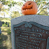 BRYAN EATON/Staff photo. One overly enthusiastic lover of Halloween put several jack-o-lanterns along the wall and this plaque at the Old Hill Cemetery on Greenleaf Street in Newburyport apparently to add some extra spookiness.