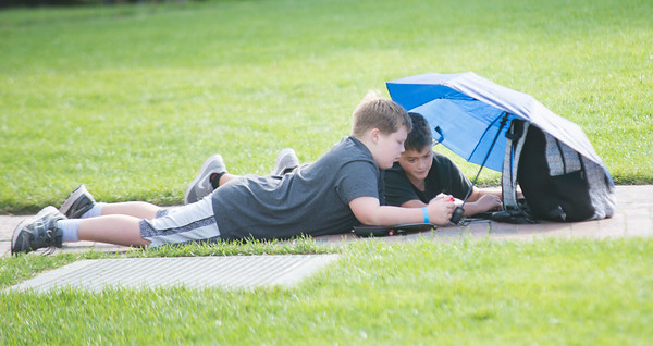 JIM VAIKNORAS/Staff photo Will Portalla, 12, and Camden Rooney, 11, use an umbrella to shade the sun as the play a game on their Nintendo Switches portable gaming system in Market Landing Park Friday afternoon.