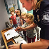 BRYAN EATON/Staff photo. Newburyport police officer Megan Tierney fingerprints Saskia Howe, 5, as her kindergarten classmates wait their turn. The Newburyport Montessori School students were touring the police station part of their learning about local institutions like the fire department, banks and library.