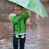JIM VAIKNORAS/Staff photo Ethan Xiao, 2, of Newburyport, tries to keep dry as he walks down Inn Street in Newburyport Monday  morning.