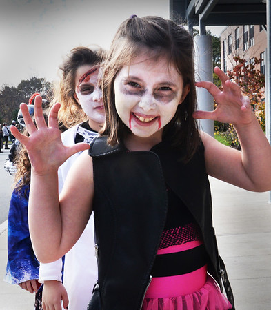 "BRYAN EATON/Staff photo. Alexa Warchos, 8, gives a scare as she plays a ""motorcyble zombie Tuesday afternoon in Newburyport's Bresnahan School Halloween Parade."