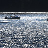 BRYAN EATON/Staff photo. A boat heads up the Merrimack River amidst the twinkling of sunligh off the water at Point Shore in Amesbury. The weather for the weekend looks fairly good for boating though the forescast mentions a shower possible.