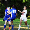BRYAN EATON/Staff photo. Georgetown's Casey Smith kicks the ball past teammate Brenna Donoghue as Amesbury's Maddie Morris moves in.
