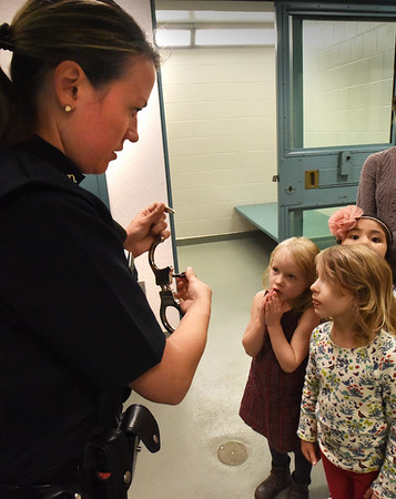 BRYAN EATON/Staff photo. Josie Wizda, left, and Saskia Howe, both 5, look as Newburyport police officer Megan Tierney shows handcuffs outside one of the jail cells.