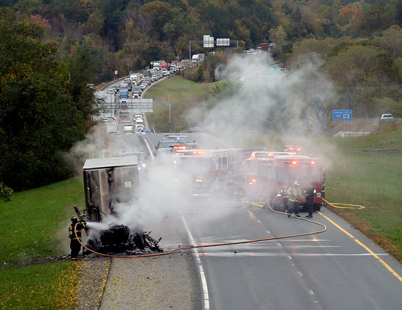 BRYAN EATON/Staff photo. Firefighters tackle a tractor trailer fire on Insterstate 495 northbound in Amesbury on Monday morning. The cab of the rig was destroyed and traffic was backed up and diverted.