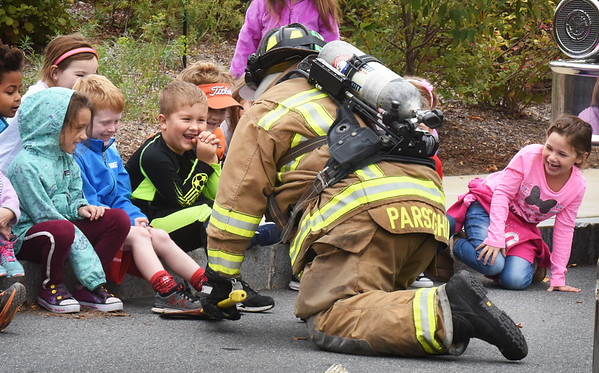 BRYAN EATON/Staff photo. Bresnahan School kindergartners react as Newburyport firefighter Ken Parseghian shows how they search buildings close to the ground when at a fire. He was giving them safety tips for Fire Safety Month.