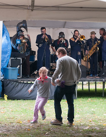 JIM VAIKNORAS/Staff photo Aaron Plotnik dances with his daughter Rebecca as The Emperor Norton's Stationary Marching Band performs at the American Music & Harvest Festival at the Spencer-Peirce-Little Farm in Newbury on Saturday.The event which featured band throughout the day, benefited area education foundations.