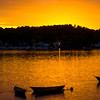 JIM VAIKNORAS/Staff photo A trio of dories are silhouetted by the setting sun along the Merrimack River in Amesbury near Lowells Boat Shop this weekend.