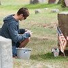 JIM VAIKNORAS/Staff photo Kyle McKendry makes a sketch of after cleaning a grave Sunday afternoon.He was on of about 50 Triton student volunteers to clean the graves of veteran's at South Byfield Cemetery.