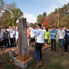 JIM VAIKNORAS/Staff photo Tracey Goodwin demostrales how to clean a grave stone Sunday afternoon. They were two of about 50 Triton student volunteers to clean the graves of veteran's at South Byfield Cemetery.